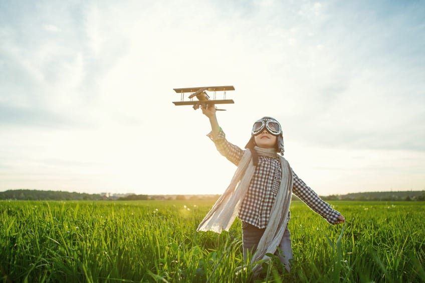 Little boy with wooden airplane in the field