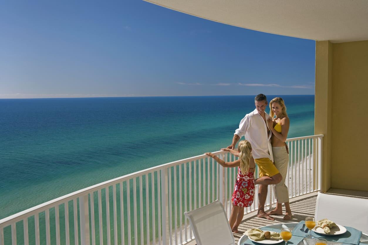 Family of Three On Hotel Balcony Overlooking Ocean